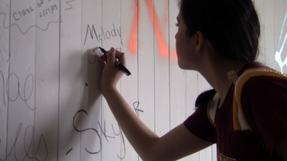 Melody Juarez writes her name on the wall on Tillman's top floor. Photos by Kris Gaitan • gaitank@mytjnow.com