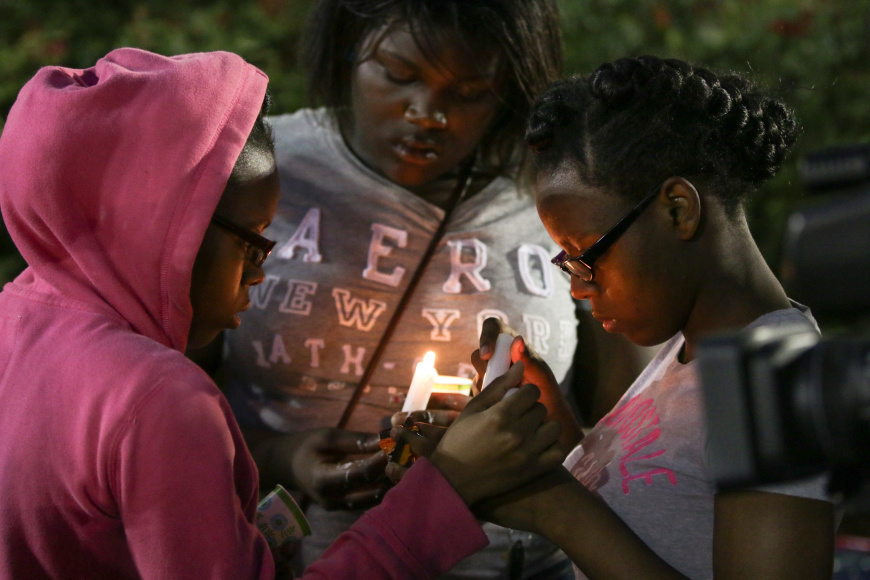 Two girls light candles in memory of Walter Scott outside of North Charleston City Hall. Jacob Hallex/ The Johnsonian